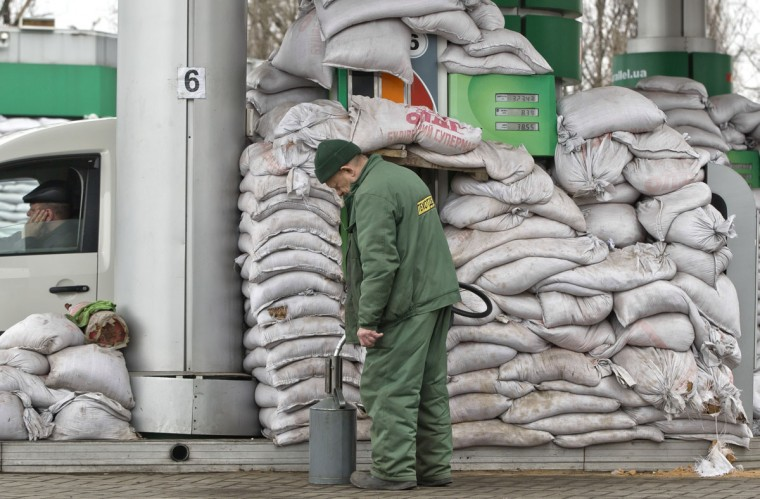"""A man pours gasoline into a canister at a fuel pump covered in sandbags to protect it from possible shelling, in Donetsk, Ukraine, Monday, March 2, 2015. More than 6,000 people have died in eastern Ukraine since the start of the conflict almost a year ago that has led to a """"merciless devastation of civilian lives and infrastructure,"""" the U.N. human rights office said Monday. (AP Photo/Vadim Ghirda)"""