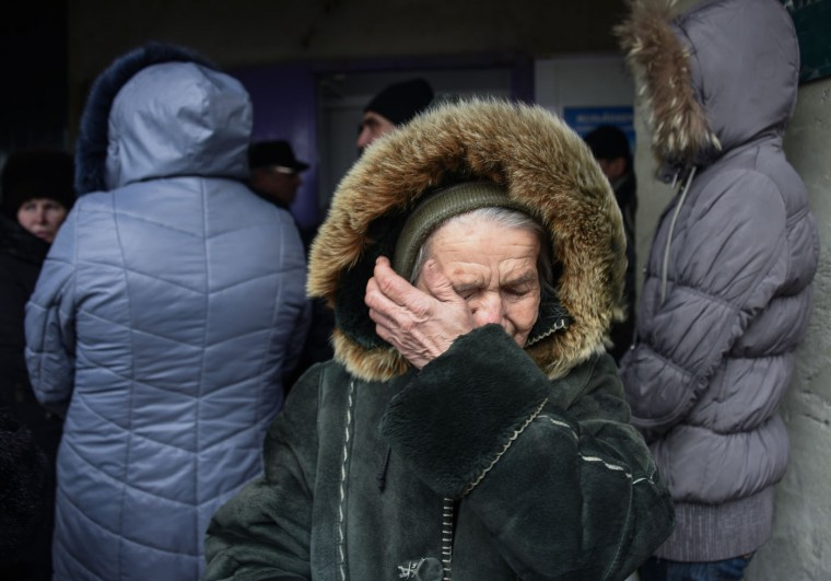 In this picture taken on March 3, 2015, Vera Pavliy, 76 year-old, dressed in a worn-out sheepskin coat, cries outside a bank in the town of Kurakhove, Ukraine, just a few miles away from the area controlled by Russia-backed rebels. The 76-year-old was stuck behind the battle lines with no money and no way to get home. The war that brought death and destruction to the region has largely abated, but the misery remains. In fact an effective government blockade on separatist-held areas is only getting worse. The goal is ostensibly to choke the rebel economy and force the separatist front to yield, but for now Kiev's actions are fostering only resentment. (AP Photo/Mstyslav Chernov)