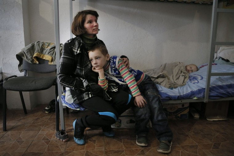 Natalya Barakhlenko and her sons, Anton, right, and Denis, who have fled their separatist-held hometown of Horlivka, sit in a hostel for the internally displaced in the government-controlled city of Slovyansk, Donetsk' region, Ukraine, Thursday, March 12, 2015. Ukraine's government reported in early March that there are almost 1.1 million registered internally displaced people across the country. (AP Photo/Efrem Lukatsky)