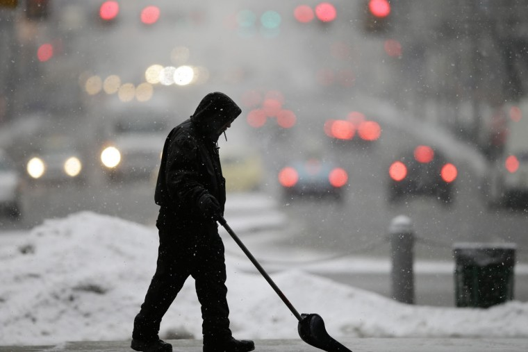 A workman clears snow Thursday, March 5, 2015, during a winter storm at City Hall in Philadelphia. The Philadelphia area was forecast to receive 5 to 8 inches of snow through Thursday, with lesser amounts to the north and more to the south. (AP Photo/Matt Rourke)
