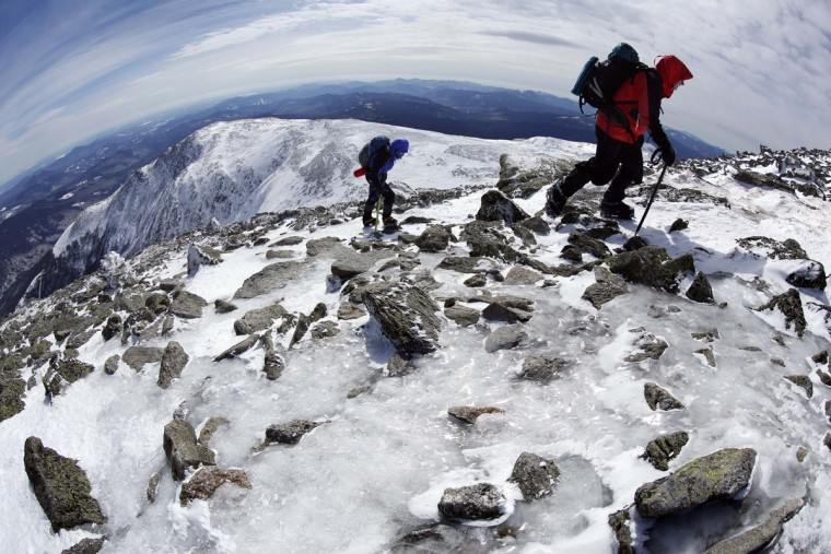 In this Tuesday, March 10, 2015 photo, Gary Gustafson, 58, leads Linda Dewey, 54, up an icy trail on the summit cone of Mount Washington in New Hampshire. The hikers waited about four weeks for a calm day before attempting the mountain that is notorious for its erratic weather. (AP Photo/Robert F. Bukaty)