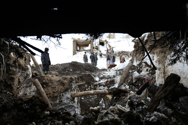 Afghans walk amid houses damaged by an avalanche in Abdullah Khil village of Panjshir province, northeast of Kabul, Afghanistan, Sunday, March 1, 2015. An Afghan provincial official says that the death toll from the massive avalanche in a mountainous valley near the capital Kabul rose to almost 200 as bulldozers and other machinery began clearing roads and rescue teams were able to reach remote villages that have been cut off for almost a week. The official said Sunday that as rescue workers dig through the snow, they are uncovering more bodies, including women and children. (AP Photo/Rahmat Gul)