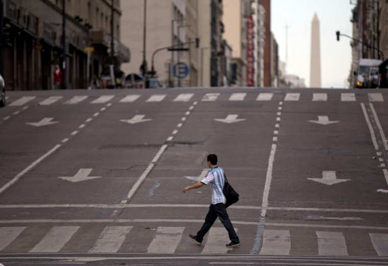 A man crosses an avenue during a transportation strike in Buenos Aires, Argentina, on Tuesday. Many businesses were shuttered and streets were mostly empty Tuesday as the country's transportation unions called a nationwide strike to protest income tax rates and high inflation in the South American country. (Natacha Pisarenko/AP)