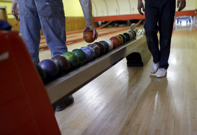 Jerry Middleton, left, picks up a duckpin bowling ball during a tournament at Shenandoah Bowling Lanes, Saturday, March 28, 2015, in Mount Jackson, Va. The sport, which is mostly played in the Mid-Atlantic, enjoyed its peak in the 1960s. (AP Photo/Patrick Semansky)