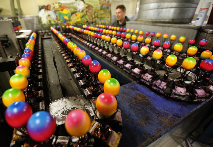A worker checks the quality of different colored eggs at the Baumeister Frischei company  in Breckerfeld, Germany, on Tuesday (Frank Augstein/AP)