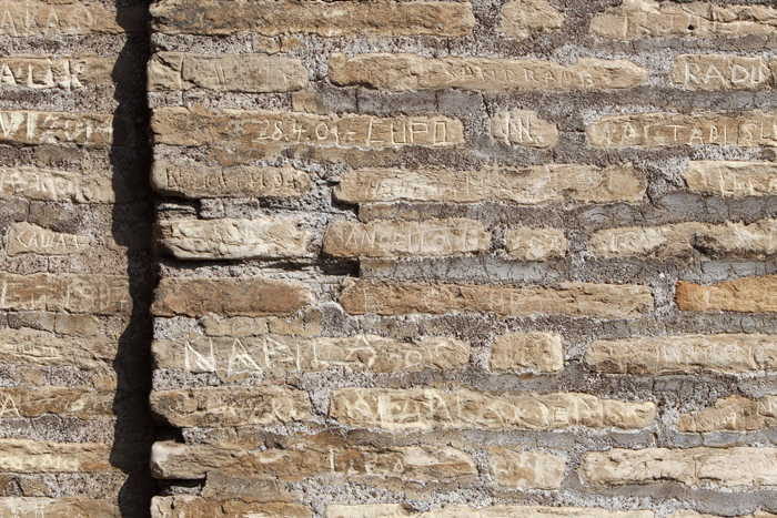 Carved writings are seen on a wall of an upper level of the Rome's Colosseum on Tuesday. Two American tourists face charges for carving their names into the Colosseum, the latest act of vandalism sustained by the ancient monument at the hands of tourists, police said Monday. The tourists from California, 21 and 25, were cited Saturday for carving their first names 3 inches high into an upper level of the Colosseum. (Riccardo De Luca/AP)