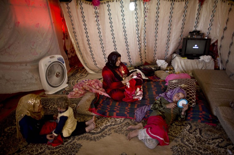 In this Friday, March 6, 2015 photo, Syrian refugee Fatima Jassim, 39, holds her newborn daughter as her other children play in their tent in an informal tented settlement in the Jordan Valley, Jordan. Jassim says she struggles to feed her newborn. ìI want to see my 3-day-old daughter Marwa grow up under a roof, safe and healthy,î she says. ìI want to give her what I could not give her elder sisters, a good childhood. (AP Photo/Muhammed Muheisen)