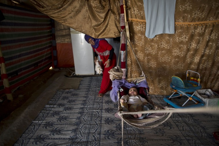 In this Monday, March 9, 2015, photo, Syrian refugee Jawahir Alhassan, 28, walks toward her son Hamza, 5 months, to change his clothes while laying in a hammock inside their tent at an informal tented settlement in Al-Aghwar, Jordan, near the border with Israel. In Jordan, most refugees settle in urban areas. Just over 100,000 live in the three main authorized refugee camps in northern Jordan. (AP Photo/Muhammed Muheisen)