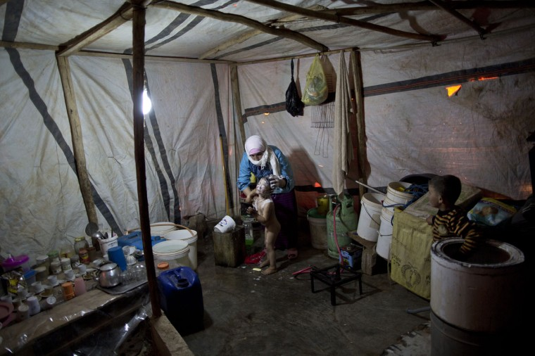 In this Sunday, March 8, 2015 photo, Syrian refugee Nisreen Sami, 23, bathes her son Mohammed, 3, at their tent in an informal tented settlement near the Syrian border, on the outskirts of Mafraq, Jordan. In Jordan, most refugees settle in urban areas. Just over 100,000 live in the three main authorized refugee camps in northern Jordan. (AP Photo/Muhammed Muheisen)