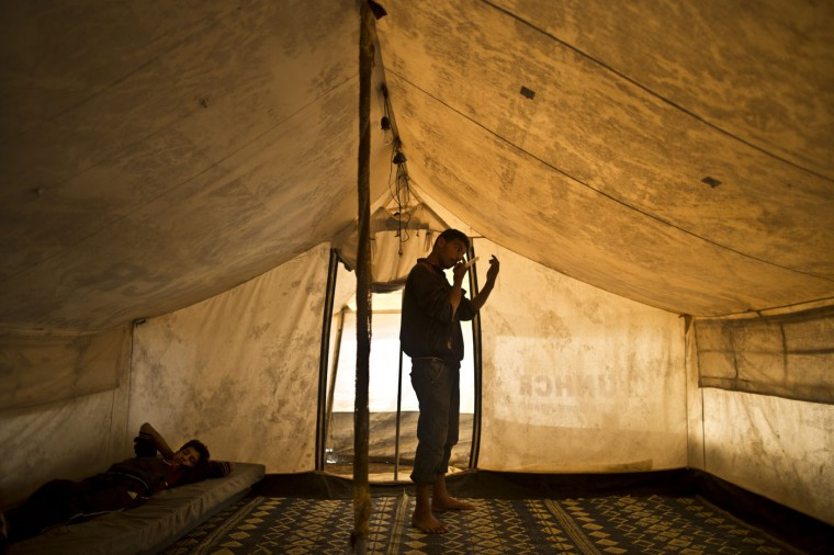 In this Friday, March 6, 2015 photo, a Syrian refugee looks at himself in a mirror while combing his hair in his tent at an informal tented settlement in the Jordan Valley, Jordan. Some refugees say they pitched tents to be close to jobs on farms, especially during harvest season. Others say they can't afford rent or that they don't want to live in the authorized camps because of restrictions there. (AP Photo/Muhammed Muheisen)