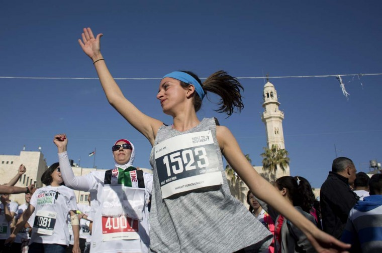 Runners warm up near the starting line of the Palestine Marathon at Manger Square, in front of the Church of Nativity in the West Bank city of Bethlehem, Friday, March 27, 2015. Three thousand Palestinian and international runners participated in the race, with the course winding through the streets of Bethlehem, past the Olympic distance track course, the Israeli separation barrier and Palestinian refugee camps.  || CREDIT: NASSER NASSER - AP PHOTO