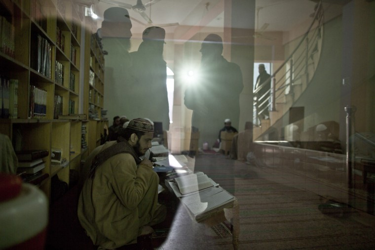 In this Sunday, Jan. 18, 2015 photo, Pakistani lecturers in a madrassa, or Islamic school, are reflected in the window of a classroom, while students attend their class at a seminary in Rawalpindi, Pakistan. (AP Photo/Muhammed Muheisen)