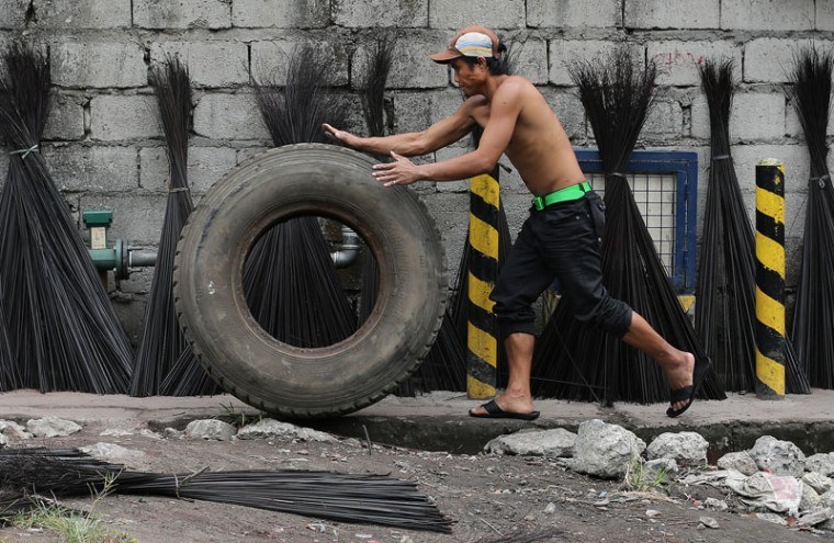 A Filipino pushes a used truck tire past handicraft materials that are being dried beside a road in Navotas city, north of Manila, Philippines on Tuesday. (Aaron Favila/AP)