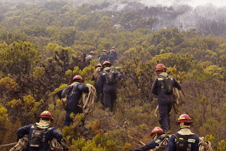 Fire fighters make their way up a hill as they battle a fire near the town of Hout Bay, South Africa, Monday, March 2, 2015. (AP Photo/Schalk van Zuydam)