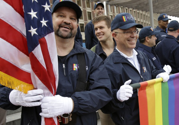 In this Nov. 11, 2014 file photo, retired U.S. Air Force Master Sgt. Eric Bullen, of Westborough, Mass., left, holds an American flag as U.S. Army veteran Ian Ryan, of Dennis, Mass., front right, rolls up an OutVets banner after marching with a group representing LGBT military veterans in a Veterans Day parade in Boston. The organizers of Boston's annual St. Patrick's Day parade voted to allow the group of gay veterans along with a second gay group, Boston Pride, to march in the parade scheduled to step off at 1 p.m., on Sunday, March 15, 2015. (AP Photo/Steven Senne, File)