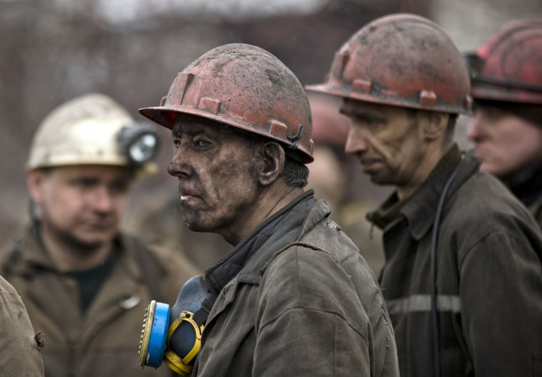 Ukrainian coal miners wait for a bus after returning to the surface of the Zasyadko mine in Donetsk, Ukraine, Wednesday, March 4, 2015. (AP Photo/Vadim Ghirda)