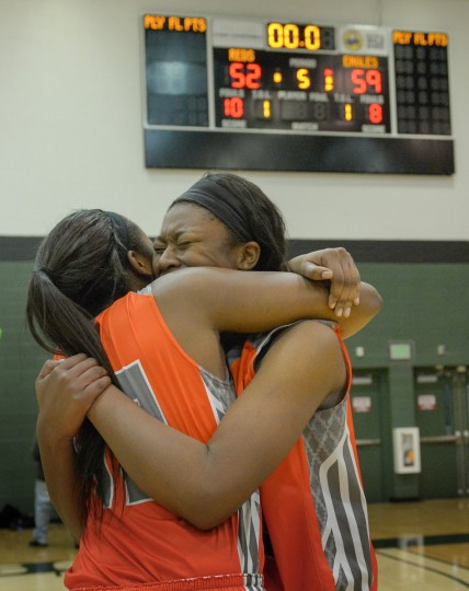 McDonogh seniors Dajah Logan (L) and Jameira Johnson embrace after McDonogh defeats Roland Park Country School, 59-52, to win the IAAM A Conference basketball championship Sunday evening at Stevenson University in Owings Mills.  (Doug Kapustin/for BSMG)