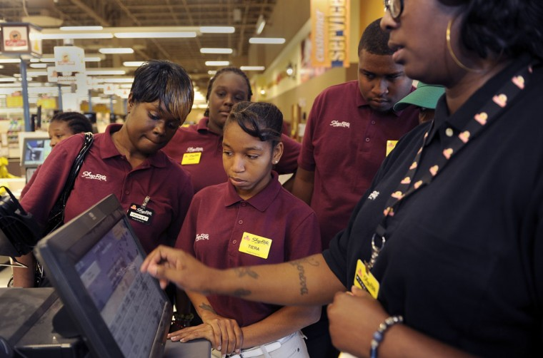 New employees receive training about procedures in the self checkout lane from bookkeeper Lerelle Washington, right, at the new ShopRite store on Liberty Heights Avenue in Howard Park. (Barbara Haddock Taylor/Baltimore Sun)