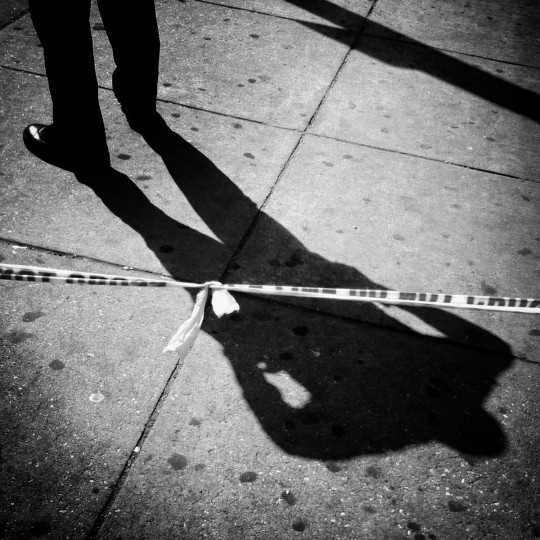 A police officer's shadow and crime scene tape at a shooting on West Saratoga Street.  (Lloyd Fox/Baltimore Sun)