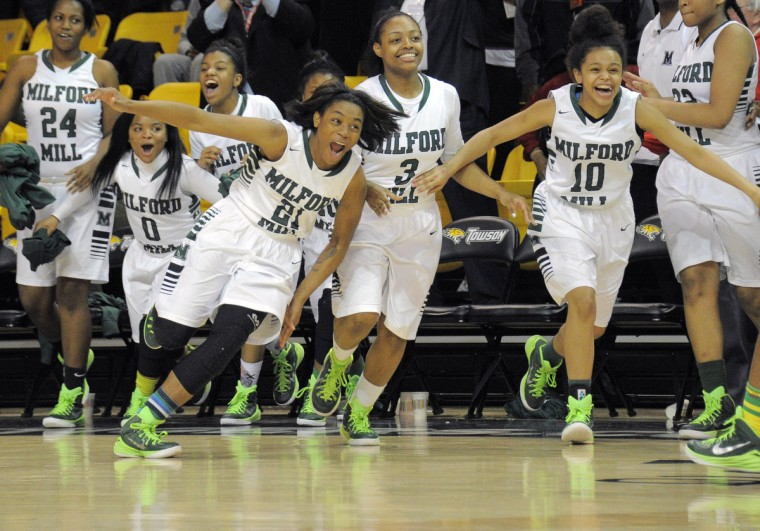 Milford Mill Millers players including Nijah Frederick (21), Makayla Pollard (3) and Caitlin King (10) rush the court as time expires against the Urbana Hawks during the MPSSAA Class 3A Final at Towson University. Milford Mill prevailed, 74-70. (Karl Merton Ferron/BSMG)