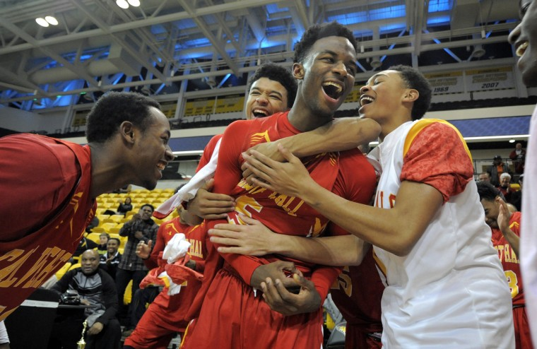 Calvert Hall #15 Nico Clareth is mobbed by teammates after he was named the tournament MVP after Calvert Hall defeated John Carroll 53-52. Calvert Hall vs. John Carroll boys high school Catholic League Championship held at the SECU Arena.  (Lloyd Fox/Baltimore Sun)