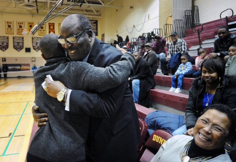 Coach Bob Wade, center, hugs his former player Muggsy Bogues as his wife Carolyn Wade smiles during the ceremony in which Dunbar High School named its basketball court Coach Wade Court. (Kenneth K. Lam/BSMG)