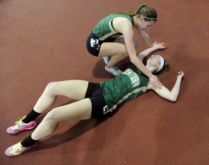 Century's Megan Callan checks on collapsed teammate Kylie Davis after Davis won the 2A Girls 300 Meter Dash during the MPSSAA State Championship Indoor Track Meet in Landover. (Dylan Slagle/BSMG)