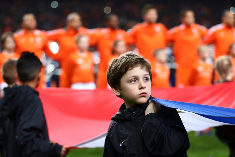 A boy holds the national flag as he stands before players of the Netherlands prior to the Euro 2016 group A qualifying soccer match between the Netherlands and Turkey at Arena stadium in Amsterdam, Netherlands. (Peter Dejong/Associated Press)