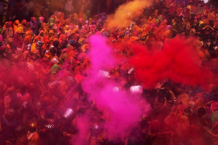 """Colored powder and water is thrown as Hindu devotees participate in """"Huranga,"""" during celebrations marking Holi, the Hindu festival of colors, at the Baldev Temple in Dauji, 180 kilometers (113 miles) south of New Delhi, India. During Huranga women playfully hit men with cloth whips as men drench them with buckets of colored water. (Bernat Armangue/Associated Press)"""