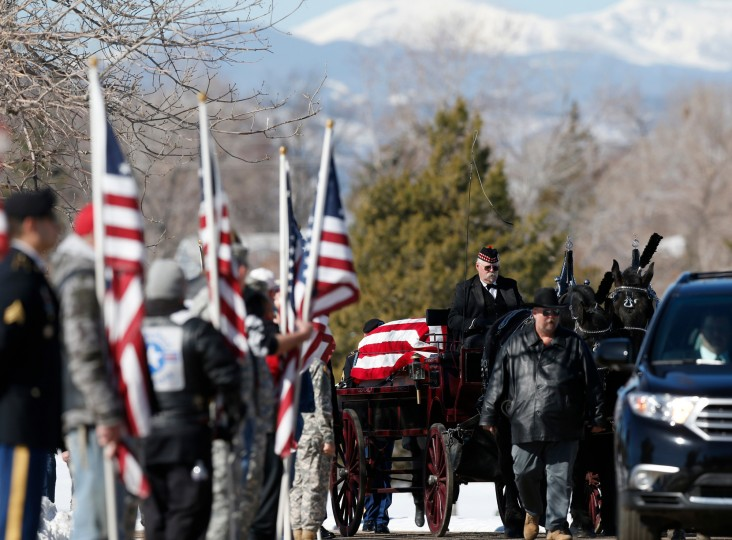 A wagon carries the casket of Korean War POW Floyd J.R. Jackson to a graveside service in Centennial, Colo. Jackson's remains were returned to Colorado 64 years after he died in an enemy prisoner of war camp. (David Zalubowski/Associated Press)