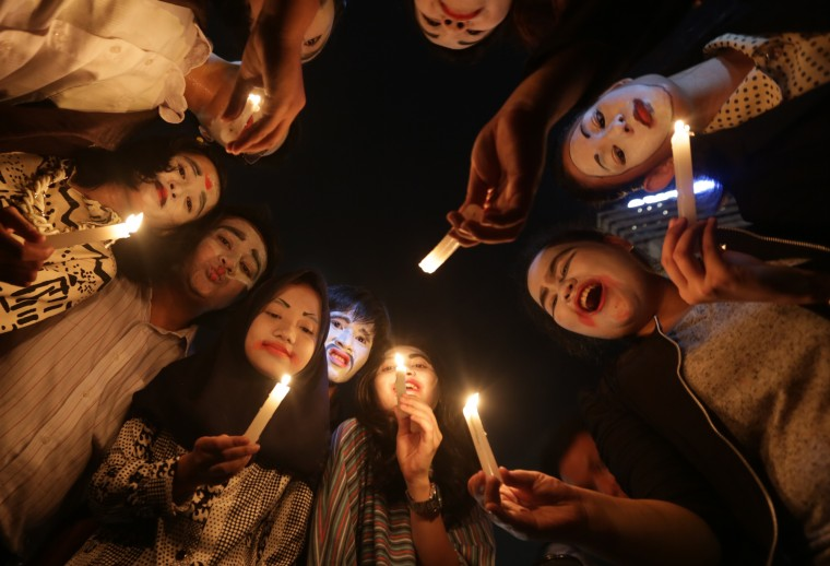 Indonesian activists hold candles during a candle light vigil marking Earth Hour, in the main business district in Jakarta, Indonesia. (Achmad Ibrahim/Associated Press)
