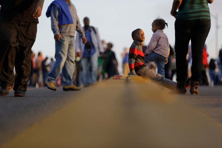 """Children and others walk and sit on the Edmund Pettus Bridge in Selma, Ala. This weekend marks the 50th anniversary of """"Bloody Sunday,"""" a civil rights march in which protesters were beaten, trampled and tear-gassed by police at the Edmund Pettus Bridge in Selma, Ala. (AP Photo/Gerald Herbert) ORG XMIT: GAMS143 (Gerald Herbert/Associated Press)"""