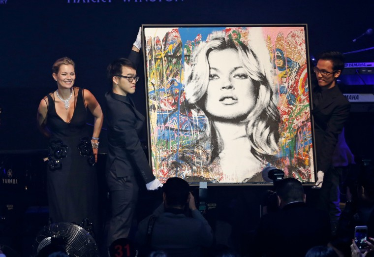 "British model Kate Moss, left, stands next to the artwork ""Kate Moss"" created by French street artist Mr. Brainwash, which is displayed for auction at the fundraising gala organized by amfAR (The Foundation for AIDS Research) in Hong Kong. (Kin Cheung/Associated Press)"