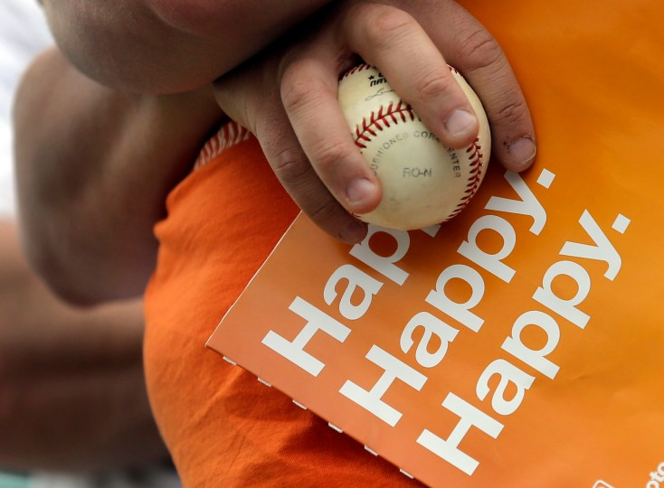 A fan holds a ball in hopes of getting an autograph before the start of an exhibition spring training baseball game between the Miami Marlins and the New York Mets in Jupiter, Fla. (Jeff Roberson/Associated Press)