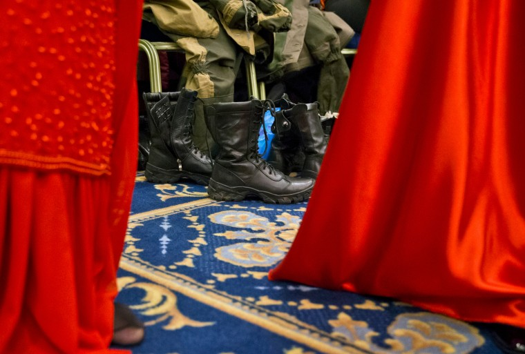 Russia-backed female rebel fighters wear evening dresses standing next to their military uniforms before taking part in a beauty contest involving women from the main separatist battalions in Donetsk, Ukraine. Self-proclaimed authorities in the rebel-held Donetsk held a beauty pageant for female rebel fighters on the eve of March 8, a women's day widely celebrated throughout the former Soviet Union. (Vadim Ghirda/Associated Press)
