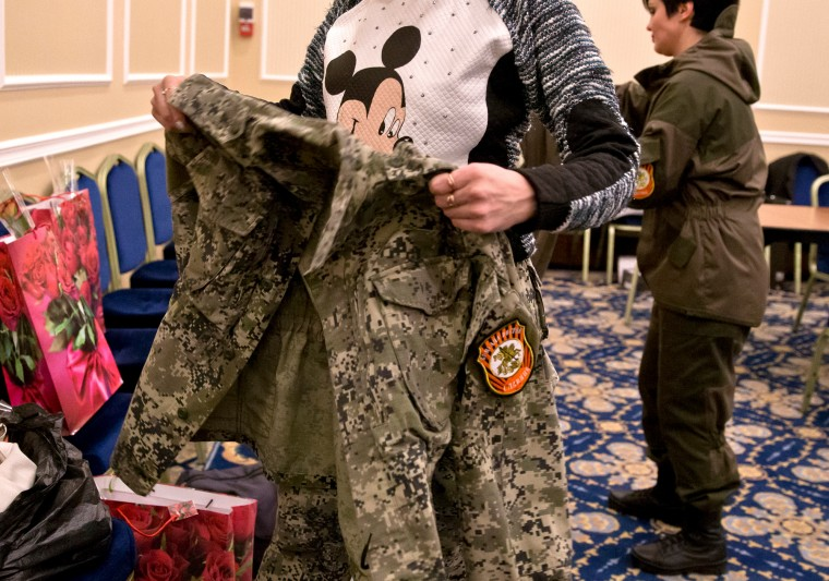 A Russia-backed female rebel fighter sporting a Mickey Mouse shirt changes back to military uniform after taking part in a beauty contest involving women from the main separatist battalions in Donetsk, Ukraine. Self-proclaimed authorities in the rebel-held Donetsk held a beauty pageant for female rebel fighters on the eve of March 8, a women's day widely celebrated throughout the former Soviet Union. (Vadim Ghirda/Associated Press)