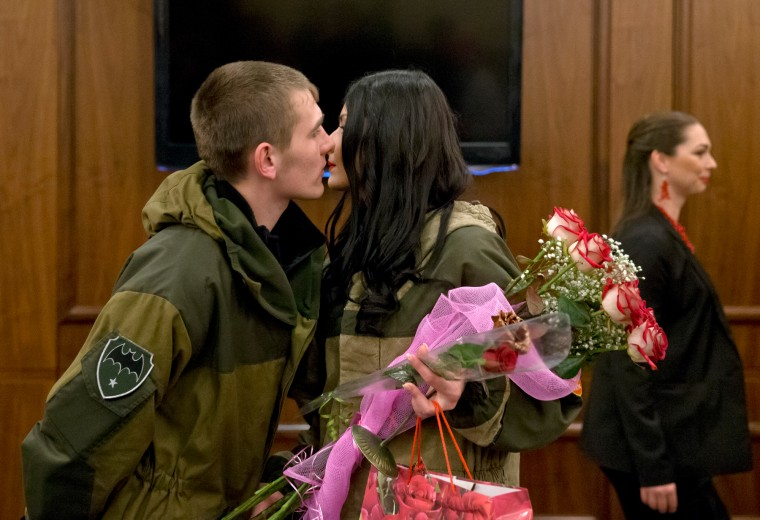 Russia-backed rebel fighters kiss after a beauty contest involving women from the main separatist battalions in Donetsk, Ukraine. Self-proclaimed authorities in the rebel-held Donetsk held a beauty pageant for female rebel fighters on the eve of March 8, a women's day widely celebrated throughout the former Soviet Union. (Vadim Ghirda/Associated Press)