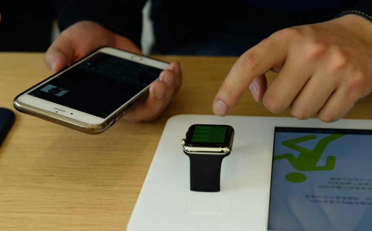 A customer holding his phone prepares to touch an Apple Watch smartwatch at an Apple Store near West Lake on April 10, 2015 in Hangzhou, Zhejiang province of China. (ChinaFotoPress/Getty Images)