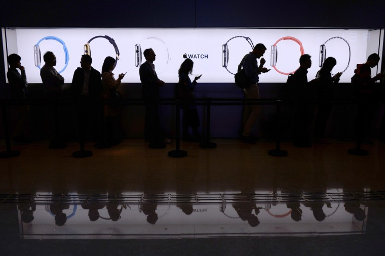 People wait in a queue to test out the new Apple Watch at a store in Hong Kong on April 10, 2015. Apple says its first wearable device will connect wirelessly to a user's iPhone and will be the interface for messaging, calls and apps, especially ones geared toward health and fitness. (Dale De La Rey/AFP/Getty Images)