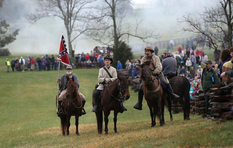 American Civil War re-enactors dressed as Confederate cavalry take part in a re-enactment of the Battle of Appomattox as spectators watch at the Appomattox Court House National Historical Park April 8, 2015 in Appomattox, Virginia. Today is the 150th anniversary of Confederate General Robert E. Lee's surrender of the Army of Northern Virginia to Union forces commanded by General Ulysses S. Grant in the McLean House at Appomattox, Virginia. The surrender marked the beginning of the end of the American Civil War in 1865. (Photo by Win McNamee/Getty Images)