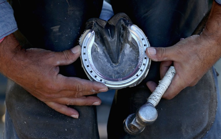 A blacksmith puts a shoe on a horse in the barn area during the morning training for the kentucky Derby at Churchill Downs on April 29, 2015 in Louisville, Kentucky. (Photo by Andy Lyons/Getty Images)