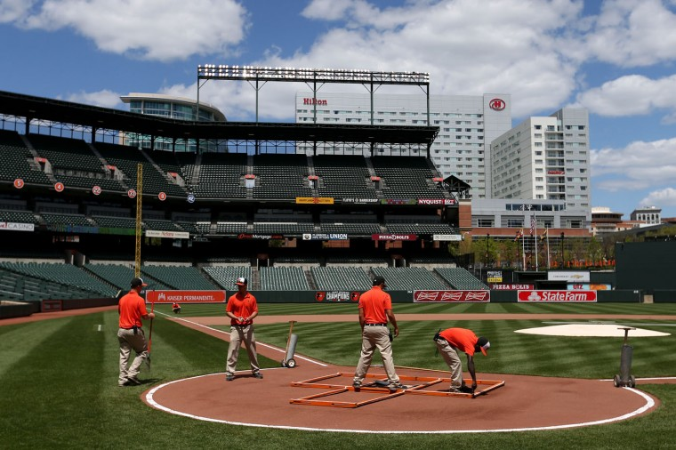 The grounds crew prepares the field before the Baltimore Orioles play the Chicago White Sox at an empty Oriole Park at Camden Yards on April 29, 2015 in Baltimore, Maryland. Due to unrest in relation to the arrest and death of Freddie Gray, the two teams played in a stadium closed to the public. Gray, 25, was arrested for possessing a switch blade knife April 12 outside the Gilmor Houses housing project on Baltimore's west side. According to his attorney, Gray died a week later in the hospital from a severe spinal cord injury he received while in police custody. (Photo by Patrick Smith/Getty Images)