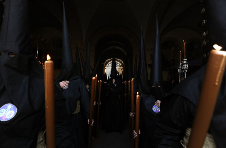 "Hooded members of the ""Los Estudiantes"" brotherhood hold candles in church before an Easter procession in Sevilla on March 31, 2015. Christian believers around the world mark the Holy Week of Easter in celebration of the crucifixion and resurrection of Jesus Christ. (AFP Photo/Cristina Quicler)"