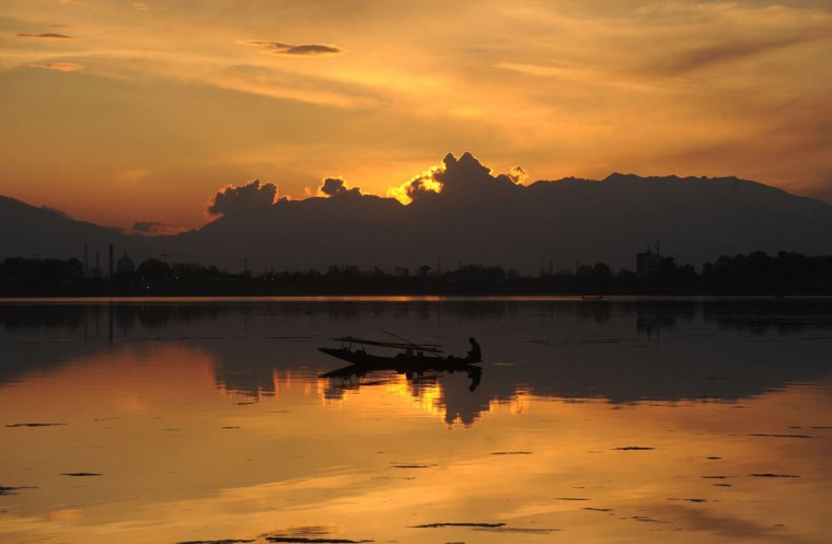 A Kashmiri fisherman paddles his boat on Dal Lake during sunset in Srinagar on April 5, 2015.The sun shined in Kashmir valley after weeks of wet weather which had brought a flood-like situation in Kashmir while National Highway 1A, the only key road connecting Kashmir to the rest of the world, opened after week long. (AFP Photo/Rouf Bhat)