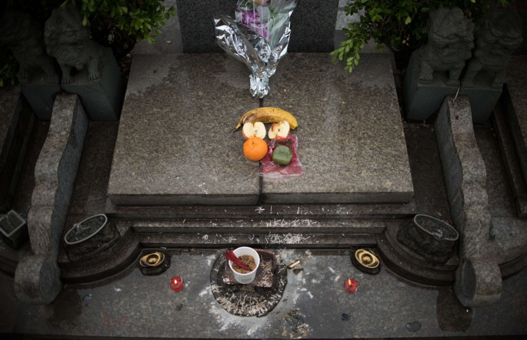 """Offerings lie on a grave during the annual """"Qingming"""" festival, or Tomb Sweeping Day, at a public cemetery in Shanghai on April 6, 2015. During """"Qingming"""" Chinese traditionally tend the graves of their departed loved ones and often burn paper money, model houses, cars, mobile phones and other goods as offerings to honour them and keep them comfortable in the afterlife. (AFP Photo/Johannes Eisele)"""