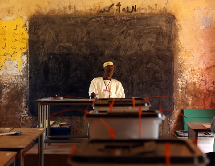 The head of a polling station waits for voters at a polling station in a classroom in Khartoum's southern suburb of Mayo on Tuesday. Mayo is mainly populated with displaced people from Darfur and Kordofan, where fighting between rebels and President Omar Al-Bashir troops has forced people from their homes. (PATRICK BAZPATRICK BAZ/AFP/Getty Images)