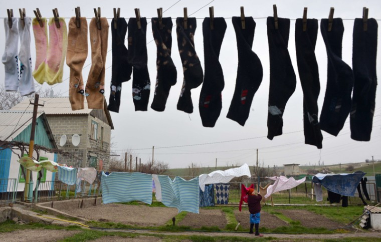 "A woman hangs washed clothes near her building on Tuesday in Berdyanske village, some 2.5 miles west from Shirokine village, where the use of heavy weapons has been reported, on the outskirts of the strategic port city of Mariupol. The French, German, Russian and Ukranian foreign ministers expressed ""grave concern"" Tuesday about violations of a shaky ceasefire in separatist-held east Ukraine but pledged to continue dialogue. (GENYA SAVILOVGENYA SAVILOV/AFP/Getty Images)"