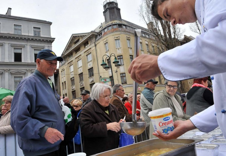 A Bosnian chef serves freshly prepared chicken soup during an attempt to make the world's largest batch of chicken soup in Sarajevo on April 17, 2015. Chefs hope to enter the Guinness Book of Records by cooking 4,124 kilograms of Bosnia's traditional Bey's soup. After the stew was ready it was shared with citizens gathered to observe this record-breaking venture.  || CREDIT: ELVIS BARUKCIC - AFP/GETTY IMAGES