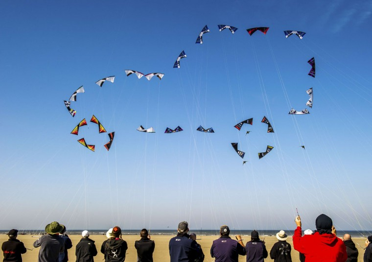 "People fly their kites to form the shape of a car in the sky on the beach in Berck, northern France, on April 20, 2015, during the 29th ""Rencontres Internationales de Cerfs Volants"" (International Kite Meeting) which runs from April 18 to 26. (AFP Photo/Philippe Huguen)"