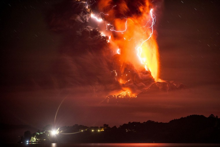 This view from Frutillar, southern Chile, shows a high column of ash and lava spewing from the Calbuco volcano, on April 23, 2015. Chile's Calbuco volcano erupted on Wednesday, spewing a giant funnel of ash high into the sky near the southern port city of Puerto Montt and triggering a red alert. Authorities ordered an evacuation for a 10-kilometer (six-mile) radius around the volcano, which is the second in southern Chile to have a substantial eruption since March 3, when the Villarrica volcano emitted a brief but fiery burst of ash and lava. (AFP Photo/P /francisco )